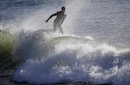 A surfer rides a wave in Half Moon Bay, Calif., Thursday, Dec. 13, 2012. The National Weather Service says so-called King Tides — caused by a rather unique combination of how the sun, the moon and the earth align — will bring the highest tides of the year on Thursday, Friday and Saturday mornings. Along with the high tides, forecasters say a building swell will bring large breaking waves to area beaches. (AP Photo/Marcio Jose Sanchez)