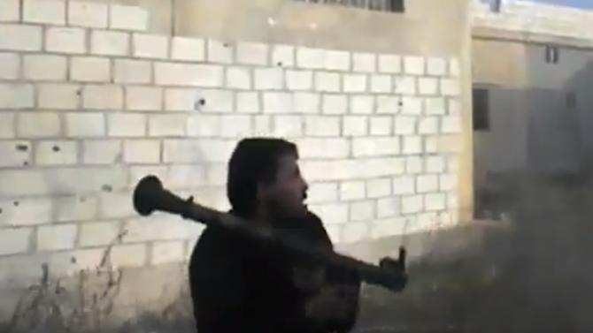 In this image taken from video obtained from the Ugarit News, which has been authenticated based on its contents and other AP reporting, a Free Syrian Army fighter reacts after firing his weapon toward a military tank, unseen, in Daraa, Syria, on Tuesday, Nov. 27, 2012. (AP Photo/Ugarit News via AP video)