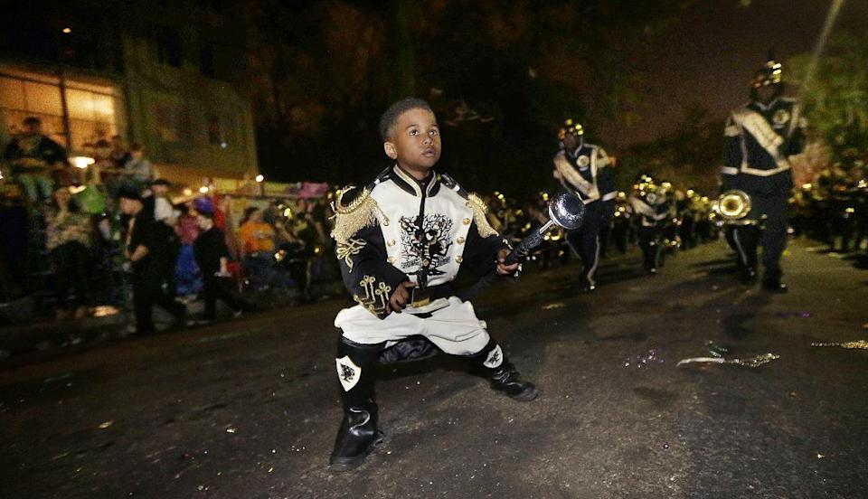 "Tudda Honore, 6, performs as a drum major with the ""Roots of Music"" marching band during the Krewe of Bacchus Mardi Gras parade in New Orleans, Sunday, Feb. 10, 2013. (AP Photo/Gerald Herbert)"