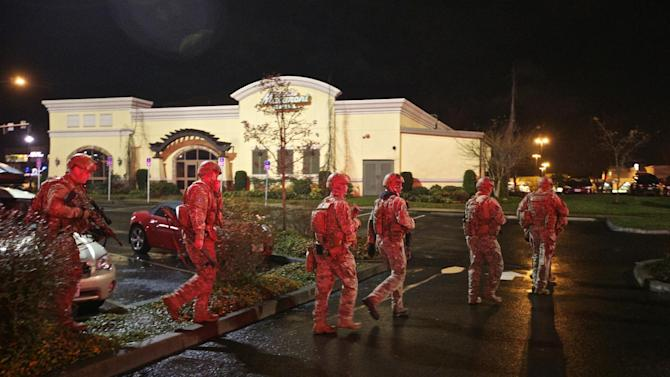 A tactical team moves through the mall parking lot at Clackamas Town Center in Portland, Ore., Tuesday, Dec. 11, 2012. Witnesses say the scene went from cheery to chaotic in seconds when a gunman opened fire in the suburban Portland shopping mall Tuesday, killing two people and wounding another. (AP Photo/The Oregonian, Thomas Boyd)