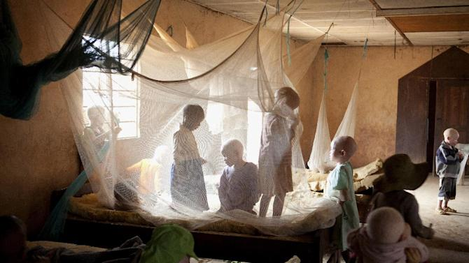 This photo taken Aug. 27, 2012 shows children playing under mosquito netting inside a dormitory of the Kabanga Protectorate Center, housed in a walled compound for the Kabanga Primary School, in Kabanga, Tanzania. The dorms are overcrowded as more people with albinism have been sent to live at the center by the government for their own safety. In danger from witch doctors, Tanzania's albinos hope their government will start to offer more help. (AP Photo/Jacquelyn Martin)