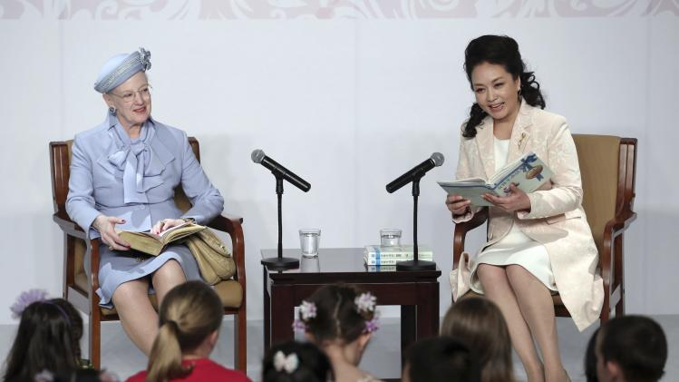 Peng Liyuan, wife of China's President Xi Jinping, reads fairy tales next to Denmark's Queen Margrethe II at a museum in Beijing