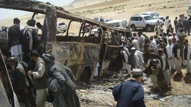FILE - In this Friday, April 26, 2013 file photo, Afghan men surround a burned bus after it collided with the wreckage of a truck that was attacked by Taliban insurgents in Maiwand district, on the highway between Kandahar and Helmand, Afghanistan. The Taliban have announced they will launch their spring offensive on Sunday, April 28, 2013, signaling plans to step up attacks as the weather warms across Afghanistan, making both travel and fighting easier. (AP Photo/Abdul Khaliq Kandahari, File)