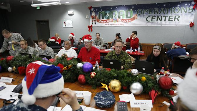 Volunteers take phone calls from children asking where Santa is and when he will deliver presents to their homes, inside a phone-in center during the annual NORAD Tracks Santa Operation, at the North American Aerospace Defense Command, at Peterson Air Force Base, Colo., Wednesday, Dec. 24, 2014. Hundreds of military and civilian volunteers at NORAD are estimated to field more than 100,000 calls this year throughout Christmas Eve, from children from all over the world eager to hear about Santa's progress. (AP Photo/Brennan Linsley)