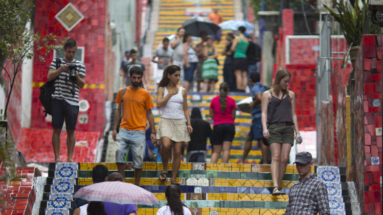 "People walk up and down a stairway that was decorated by Chilean artist Jorge Selaron, which he titled the ""Selaron Stairway"" in Rio de Janeiro, Brazil, Thursday, Jan. 10, 2013. Selaron, an eccentric Chilean artist and longtime Rio resident who created a massive, colorful tile stairway in the bohemian Lapa district that's popular with tourists, was found dead on the stairway on Thursday. He was 54. Authorities are investigating the cause of death. (AP Photo/Felipe Dana)"