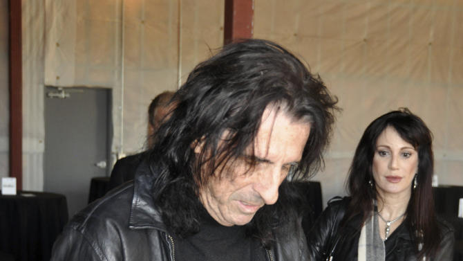 Heavy metal icon Alice Cooper signs a CD as his wife, Sheryl, looks on, Wednesday, Oct. 10, 2012, in Sioux Falls, S.D. Cooper was in South Dakota to help his friend, Dollar Loan Center majority owner Chuck Brennan, open a 6,000-square-foot rock ëní roll academy that will be open exclusively to Boys and Girls Clubs members. (AP Photo/Dirk Lammers)