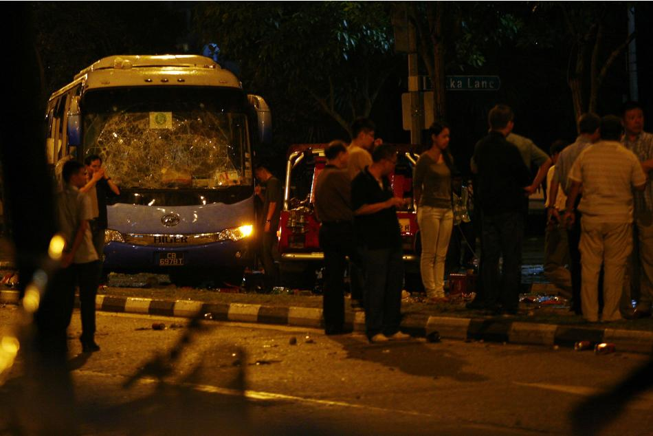 Officials stand around a bus with a smashed windshield following a riot in Singapore's Little India district
