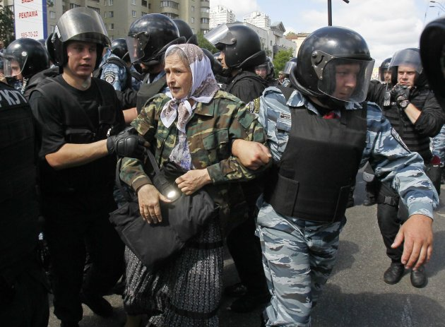 Riot police try to stop an Orthodox Christian activist as she protests against the march of gay rights activists across Kiev