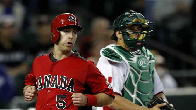 Canada's Taylor Green (5) scores on a hit by Justin Morneau as Mexico's Humberto Cota waits for the throw during the first inning of a World Baseball Classic game, Saturday, March 9, 2013, in Phoenix. (AP Photo/Matt York)