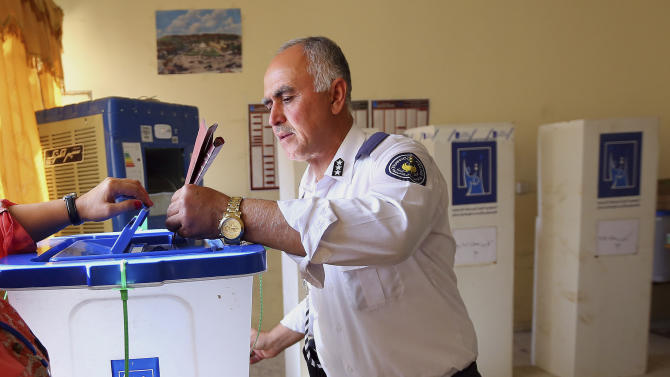 A traffic policeman casts his vote during early voting for security forces in Irbil, 350 kilometers (217 miles) north of Baghdad, Iraq, Thursday, Sept. 19, 2013. Tens of thousands of security forces in Iraq's self-ruled northern Kurdish region flocked on Thursday to polling centers to vote, two days ahead of the area's fourth election for local parliament since 1992. (AP Photo)