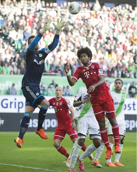 Wolfsburg goalkeeper Diego Benaglio of Switzerland, left, makes a save against Bayern's Dante of Brazil, right, during the German Bundesliga soccer match between VfL Wolfsburg and Bayern Munich in