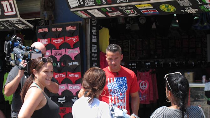 """Michael """"The Situation"""" Sorrentino speaks with Michelle Diaz, left, Patricia Garcia,  center, and Lisa Rodriguez, right, all of Philadelphia, on the boardwalk in Seaside Heights, N.J. during a break in taping of an episode of the MTV series """"Jersey Shore,"""" Friday, July 15, 2011. A new nationwide poll finds the show's depiction of a group of hard-drinking, foul-mouthed 20-somethings has not hurt New Jersey's national image, and may help it in some small ways. (AP Photo/Wayne Parry)"""