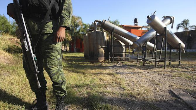 """FILE - In this Feb. 9, 2012, file photo a soldier stands in what was identified as """"metal reactors"""" after a seizure of a large clandestine methamphetamine lab at a ranch in Tlajomulco de Zuniga, on the outskirts of Guadalajara, Mexico. Soldiers made a historic seizure, 15 tons of pure methamphetamine, a haul that could have supplied 13 million doses worth over $4 billion.  (AP Photo/Bruno Gonzalez, File)"""
