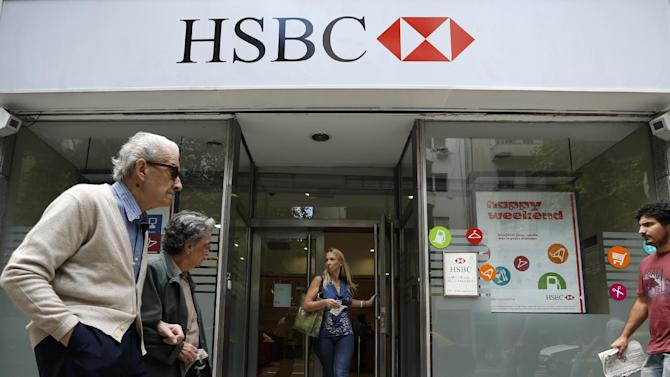 People walk in front of an HSBC branch in Buenos Aires, Argentina, Monday, March 18, 2013. Argentina's government tax chief, Ricardo Echegaray, accused the local subsidiary of the British banking giant HSBC of creating an illegal scheme that helped its clients evade more than US$100 million in taxes. (AP Photo/Victor R. Caivano)
