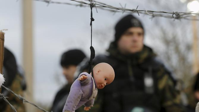 A doll, placed by stranded Iranian migrant protesters, hangs from barbed wire in front of Madedonian police at the Greek-Macedonian border near to the Greek village of Idomeni