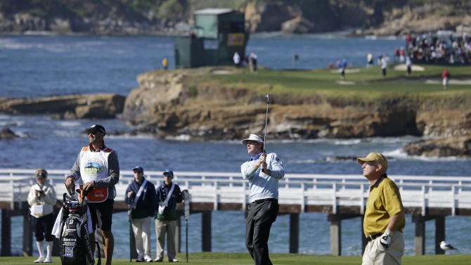 Brandt Snedeker, second from right, follows his shot from the fairway up to the fourth green of the Pebble Beach Golf Links as playing partner Toby S. Wilt, right, watches during the final round of the AT&T Pebble Beach Pro-Am golf tournament on Sunday, Feb. 10, 2013, in Pebble Beach, Calif. (AP Photo/Eric Risberg)