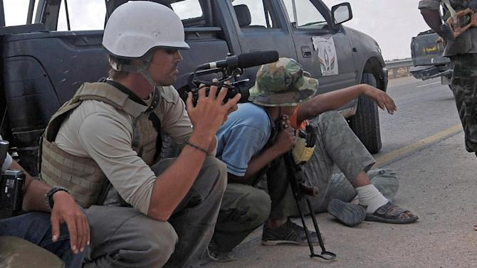A picture taken on September 29, 2011 shows US freelance reporter James Foley (L) on the highway between the airport and the West Gate of Sirte, Libya