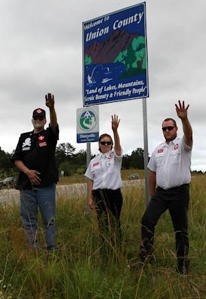 """From left, Knighthawk, April Hanson and her husband Harley Hanson, members of the International Keystone Knights Realm of Georgia, perform a traditional Klan salute along the portion of highway they want to adopt allowing them to put up a sign and do litter removal near Blairsville, Ga., Sunday, June 10, 2012. The Ku Klux Klan group wants to join Georgia's """"Adopt-A-Highway"""" program for litter removal, which could force state officials to make difficult decisions on the application. (AP Photo/The Atlanta Journal-Constitution, Curtis Compton)"""