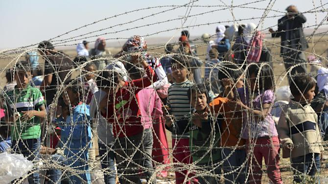 Several hundred Syrian refugees wait to cross into Turkey at the border in Suruc, Turkey, Sunday, Sept. 21, 2014. Turkey opened its border Saturday to allow in up to 60,000 people who massed on the Turkey-Syria border, fleeing the Islamic militants' advance on Kobani. (AP Photo/Burhan Ozbilici)