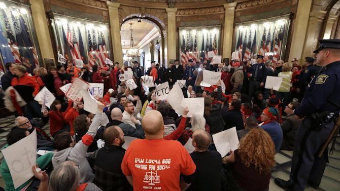 Protesters sit in the rotunda of the State Capitol in Lansing, Mich., Tuesday, Dec. 11, 2012. The crowd is protesting right-to-work legislation passed last week. Michigan could become the 24th state with a right-to-work law next week. Rules required a five-day wait before the House and Senate vote on each other's bills; lawmakers are scheduled to reconvene Tuesday and Gov. Snyder has pledged to sign the bills into law. (AP Photo/Paul Sancya)