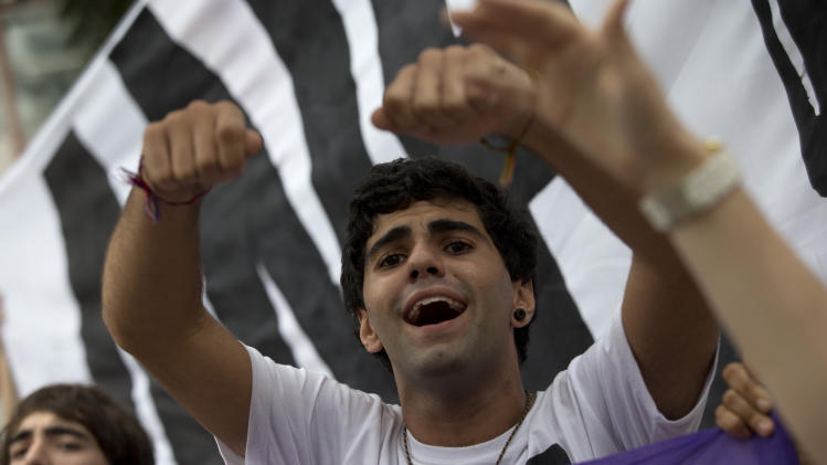 A man shouts slogans as demonstrators march toward the Maracana stadium ahead of the Confederations Cup final in Rio de Janeiro, Brazil, Sunday, June 30, 2013. Protesters have taken to the streets all over Brazil in the past two weeks, calling for a wide-range of reforms. Public approval of Brazilian President Dilma Rousseff's government has suffered a steep drop in the weeks since massive protests broke out across the country, according to Brazil's first nationwide poll released since the unrest began.(AP Photo/Silvia Izquierdo)