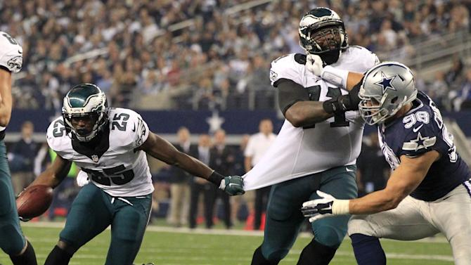 Philadelphia Eagles running back LeSean McCoy (25) grabs the jersey of Jason Peters (71) in an effort to shoot through the gap as Dallas Cowboys defensive tackle Tyrone Crawford (98) closes in for the tackle during the first half of an NFL football game, Thursday, Nov. 27, 2014, in Arlington, Texas