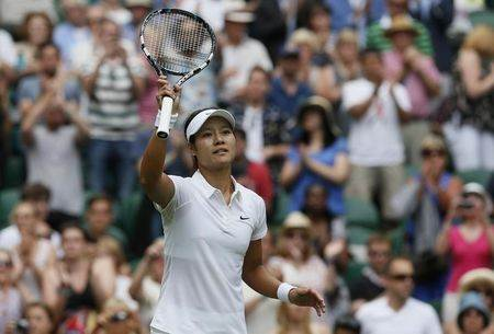Li Na of China reacts after defeating Paula Kania of Poland in their women's singles tennis match at the Wimbledon Tennis Championships, in London