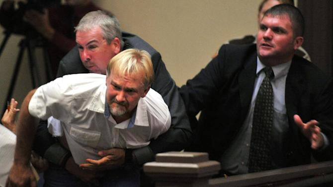 Wesley Thomas, the step father of Tiffany York, is tackled by courtroom security during the hearing of defendant Sgt. Anthony Peden  at Long County Superior Court, Thursday Aug. 30, 2012, in Ludowici, Ga.   District Attorney Tom Durden announced in court that he will seek the death penalty for Peden,  Pvt. Isaac Aguigui, and Pvt. Christopher Salmon. The three Fort Stewart soldiers are accused of malice murder, felony murder and criminal gang activity in the Dec. 4 slayings of former soldier Michael Roark and his girlfriend, 17-year-old Tiffany York. The two were found shot to death off a dirt road near the Army post. Prosecutors say the accused men were part of a militia operating within the U.S. Army that was stockpiling weapons and wanted to overthrow the federal government.  (AP Photo/Stephen Morton)