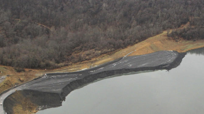This Dec. 3, 2012 photo provided by the W.Va. Department of Environmental Protection shows the embankment after a collapse at the Consol's Robinson Run operation in Harrison County, W. Va.  Crews continued to look for a missing miner and bulldozer that slid into the impoundment with two trucks and two engineers when an embankment under construction internal to the impoundment collapsed around noon on Friday, Nov. 30. (AP Photo/W.Va. Department of Environmental Protection)