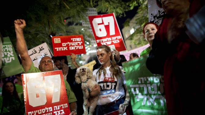 """Israeli left wing activists support the Palestinian U.N. bid for observer state status, during a rally in Tel Aviv, Israel, Thursday, Nov. 29, 2012. The Palestinians are certain to win U.N. recognition as a state on Thursday but success could exact a high price: delaying an independent state of Palestine because of Israel's vehement opposition. Hebrew on sign reads: """"Jews and Arabs refuse to be enemies."""" (AP Photo/Oded Balilty)"""