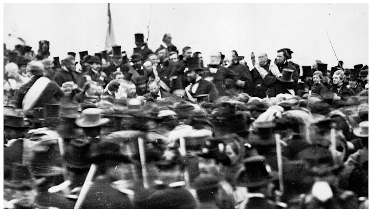 "This combination image shows, top, a photo made available by the Library of Congress of Lincoln's ""Gettysburg Address,"" on Nov. 19, 1863, in Gettysburg, Pa. and bottom, re-enactors demonstrating a cavalry battle near spectators during ongoing activities commemorating the 150th anniversary of the Battle of Gettysburg, Saturday, June 29, 2013, at Bushey Farm in Gettysburg, Pa. More than 200,000 people, including 20,000 re-enactors, are expected to visit the small Pennsylvania town for events through Fourth of July weekend to mark the 150th anniversary of the Civil War's pivotal battle. (AP Photo)"