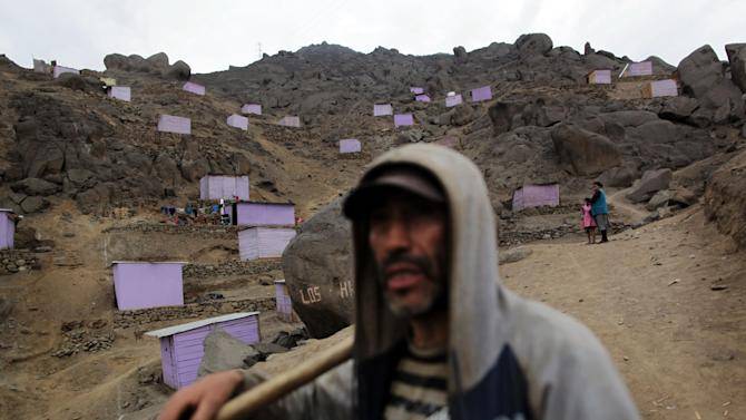 In this Oct. 17, 2012 photo, Doris Morante, behind right, stands with her daughter Galia, 6, amid new shacks built on a hill in San Juan de Lurigancho on the outskirts of Lima, Peru. Seismologists, engineers and civil defense officials agree that Lima is due for an earthquake but is acutely vulnerable and sorely unprepared. More than two in five of capital residents inhabit rickety structures built on unstable, sandy soil and wetlands, which amplify a quake's destructive power, or in the hillside settlements ringing the capital that sprang up spontaneously over a generation as people fled conflict and poverty in the interior, experts say. (AP Photo/Rodrigo Abd)