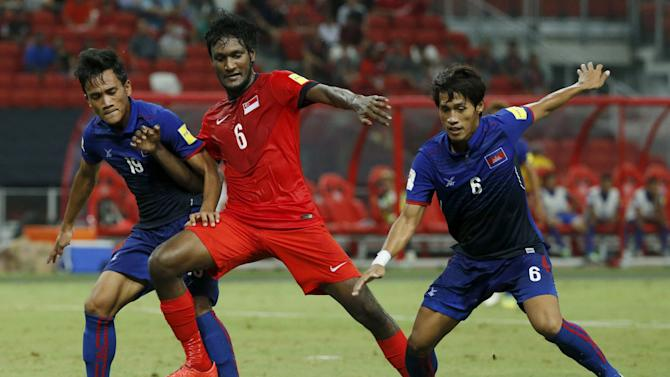Singapore's Madhu Mohana is challenged by Cambodia's Nhim Sovannara and Sam Oeun Pidor during their 2018 World Cup Group E qualifying soccer match at the National Stadium in Singapore