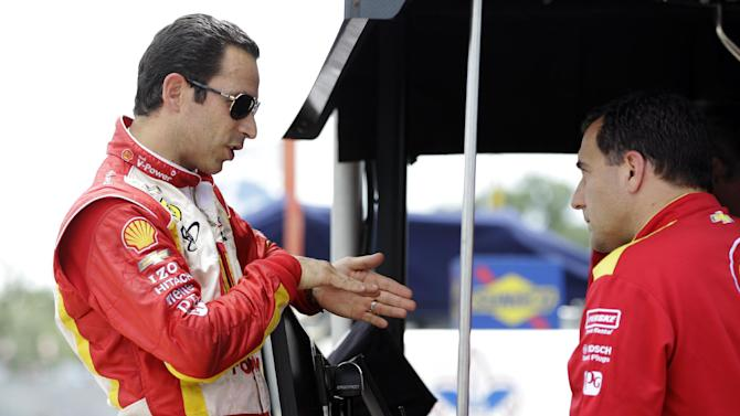 Helio Castroneves, left, talks with chief engineer Ron Ruzewski after a practice session for IndyCar's Detroit Grand Prix auto race on Belle Isle in Detroit, Sunday, June 3, 2012. (AP Photo/Carlos Osorio)