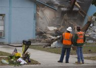 Demolition crews watch as the house, where Jeffrey Bush was swallowed by a sinkhole, is demolished in Seffner, Florida March 3, 2013. REUTERS/Scott Audette