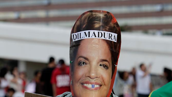 "A demonstrator wearing a mask of Brazil's President Dilma Rousseff holds a protest sign that reads in Portuguese ""No vandalizing, arrest corrupt politicians"" during a protest against sexism and in defense of women's rights in Brasilia, Brazil, Saturday, June 22, 2013. The sign on Rousseff's head is a play on words that means ""Iron Dilma.""A career technocrat and trained economist, Rousseff's tough managerial style under Silva earned her the moniker ""the Iron Lady,"" a name she has said she detests. (AP Photo/Eraldo Peres)"