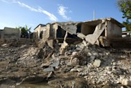 Homes lay in ruins after heavy rain brought by Hurricane Sandy destroyed them in Port-au-Prince, Haiti, Monday, Nov. 12, 2012. The rain has tapered off and floodwaters no longer claw at houses, but the situation across much of Haiti remain grim, following an autumn of punishing rains that have killed scores of people and that threaten to cause even more hunger across the nation. (AP Photo/Dieu Nalio Chery)