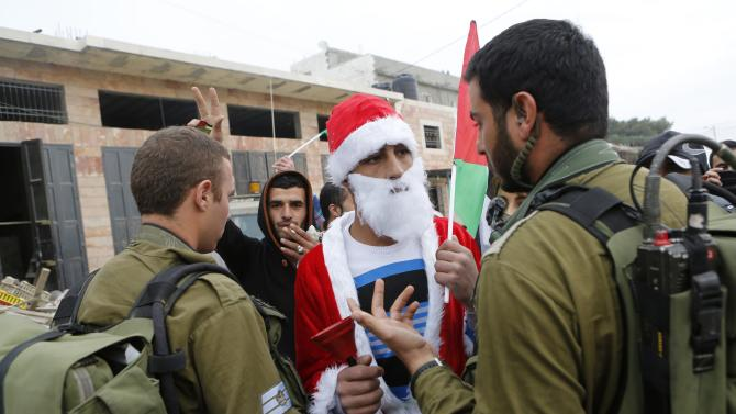 Palestinian protester dressed as Santa Claus argues with an Israeli soldier during a demonstration against Israeli settlements in the village of Maasara near the West Bank city of Bethlehem