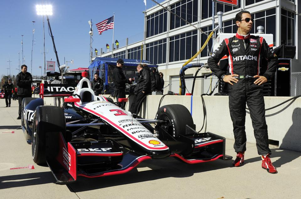 Helio Castroneves, of Brazil, stands next to his car in the pits at Barber Motorsports Park during IndyCar testing Tuesday, March 12, 2013, in Birmingham, Ala. (AP Photo/AL.com, Joe Songer) MAGS OUT