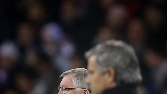 Manchester United coach Alex Ferguson, left, and Real Madrid's coach Jose Mourinho from Portugal, right, look on  during a Champions League round of 16 first leg soccer match at the Santiago Bernabeu stadium in Madrid, Wednesday Feb. 13, 2013. (AP Photo/Daniel Ochoa de Olza)