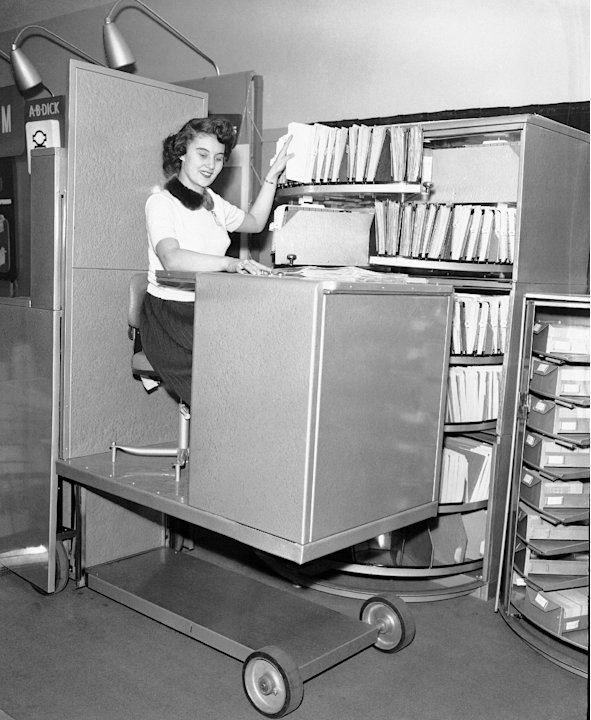 FILE - In this March, 6, 1953, file photo, Jane Martin remains seated and files paperwork using a hydraulic lift in Chicago, Ill.  An Associated Press investigation released in January 2013 found that