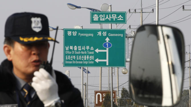 A South Korean security guard works to turn back vehicles as they were refused to enter to Kaesong, North Korea, at the customs, immigration and quarantine office in Paju, South Korea, near the border village of Panmunjom, Thursday, April 4, 2013. North Korea on Wednesday barred South Korean workers from entering a jointly run factory park just over the heavily armed border in the North, officials in Seoul said, a day after Pyongyang announced it would restart its long-shuttered plutonium reactor and increase production of nuclear weapons material. (AP Photo/Ahn Young-joon)