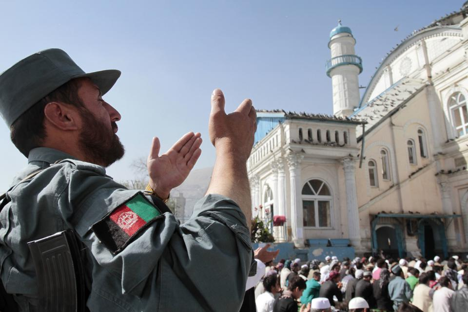 An Afghan policeman offers Eid al-Fitr prayers with others outside Shah-e- Dushamshera's mosque that marks the end of holy fasting month of Ramadan in Kabul, Afghanistan, Sunday, Aug. 19, 2012. Muslims celebrate the Eid al-Fitr around the world. (AP Photo/Musadeq Sadeq)