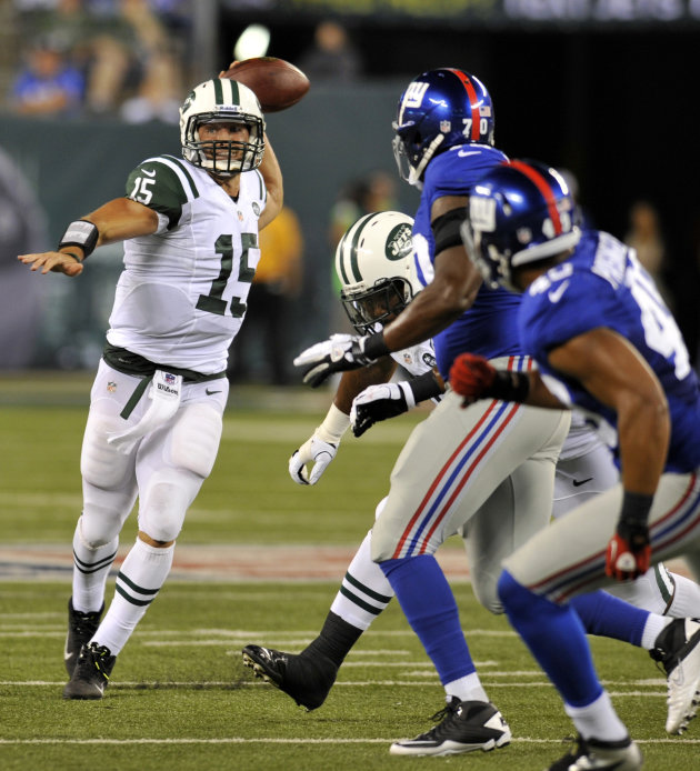 New York Jets quarterback Tim Tebow,left,  looks to throw past New York Giants defenders during the second half of a preseason NFL football, Saturday, Aug. 18, 2012, in East Rutherford, N.J.  (AP Phot