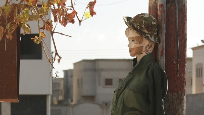 A personnel of pro-government Libyan forces, who are backed by locals, arranges a mannequin as a decoy against snipers during clashes in Benghazi