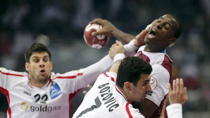 Capote of Qatar is blocked by Wagesreiter and Bozovic of Austria during the round of 16 match of the 24th men's handball World Championship in Doha
