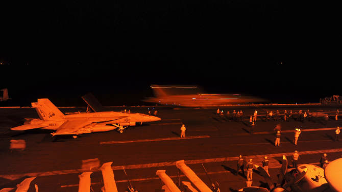 In this photo released by the U.S. Navy, A-18E Super Hornet, attached to Strike Fighter Squadron (VFA) 31, and an F/A-18F Super Hornet, attached to Strike Fighter Squadron (VFA) 213, prepare to launch from the flight deck of the aircraft carrier USS George H.W. Bush (CVN 77) to conduct strike missions against Islamic State group targets, in the Arabian Gulf, Tuesday, Sept. 23, 2014. Syria said Tuesday that Washington informed President Bashar Assad's government of imminent U.S. airstrikes against the Islamic State group, hours before an American-led military coalition pounded the extremists' strongholds across northern and eastern Syria. (AP Photo/Robert Burck, U.S. Navy)
