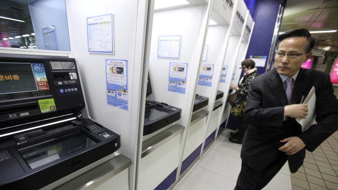 A depositor leaves after checking his account through an automated teller machine at a subway station as the bank's computer networks was paralyzed in Seoul, South Korea, Wednesday, March 20, 2013. Police and South Korean officials were investigating the simultaneous shutdown Wednesday of computer networks at several major broadcasters and banks. While the cause wasn't immediately clear, speculation centered on a possible North Korean cyberattack. (AP Photo/Ahn Young-joon)