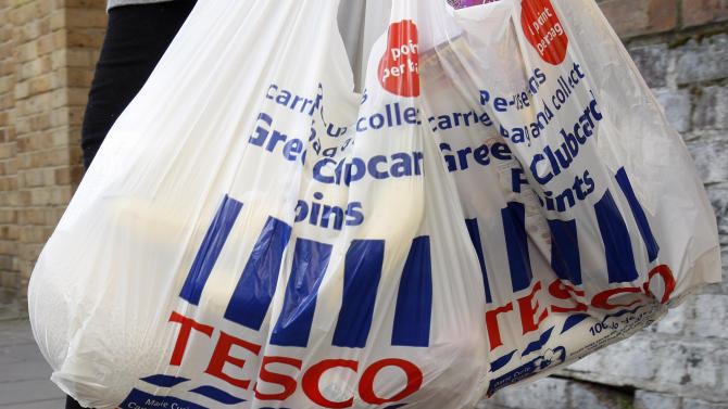 FILE - A Tuesday, April 21, 2009 photo from files showing Tesco shopping  bags abeing carried in London. The Irish food safety watchdog says that it has found traces of horse DNA in burger products sold by some of the country's biggest supermarkets, including a burger sold by global retailer Tesco that authorities said was made of roughly 30 percent horse. The Food Safety Authority of Ireland also said Tuesday that it had found traces of pig DNA in 85 percent of the burger products it tested in Irish supermarkets, including those operated by U.K-based Iceland and German discounter Lidl. (AP Photo/Kirsty Wigglesworth, File)