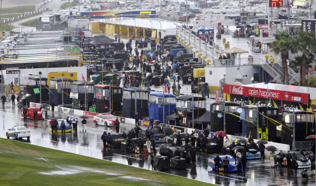 Crew members push cars into the garage after NASCAR postponed the Daytona 500 auto race in Daytona Beach, Fla., Sunday, Feb. 26, 2012, due to rain. The race has been rescheduled for Monday afternoon.